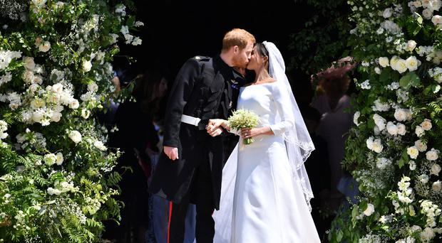 Prince Harry and Meghan Markle kiss as they leave St George's Chapel in Windsor Castle after their wedding ceremony (Ben Stansall/PA)