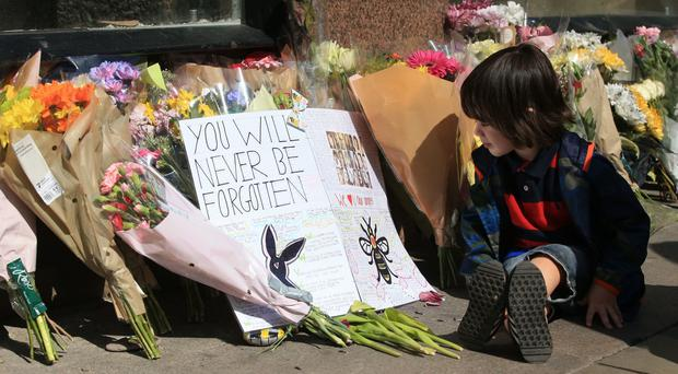 A boy studies messages left in Manchester