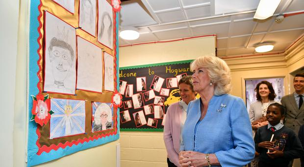 The Duchess of Cornwall looks at pictures drawn by pupils (Ben Birchall/PA)