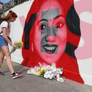 A woman lays flowers next to a mural of Savita Halappanavar (Niall Carson/PA)