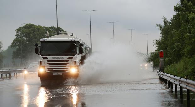 Traffic on the M42 goes through standing water after heavy rain (David Davies/PA)