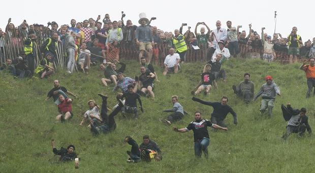Competitors take part in the annual cheese rolling competition at Cooper's Hill in Brockworth, Gloucestershire (Aaron Chown/PA)