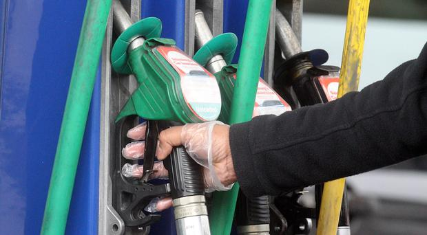 A person holding a petrol nozzle at a fuel station (Lewis Whyld/PA)