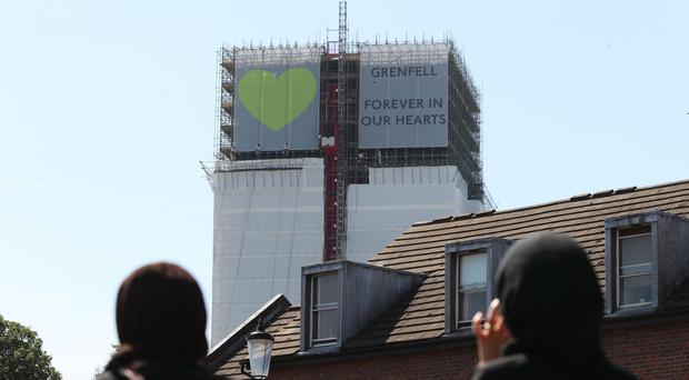 Banners are unveiled on the outside of Grenfell Tower in west London (PA)