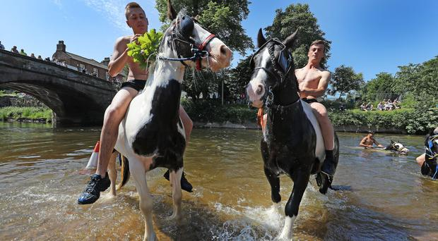 People riding horses in the river Eden during the Horse Fair in Appleby (Owen Humphreys/PA)