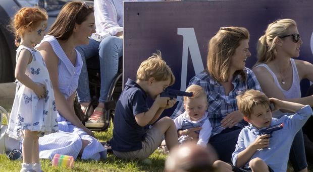 Prince George plays with toy gun at the polo