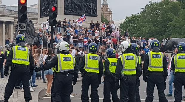 Police watch supporters of Tommy Robinson during their protest in Trafalgar Square (Tess de la Mere/PA)