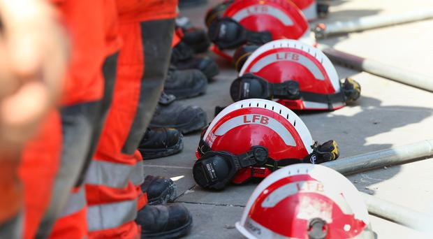 Firefighters lay their helmets on the ground as they observe a minute's silence near to Grenfell Tower (Jonathan Brady/PA)