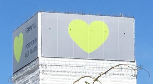 The green Grenfell heart at the top of the covered-up high-rise (London Fire Brigade/PA)