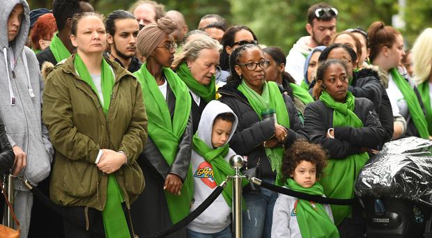 People arrive for the anniversary national minute silence and mosaic unveiling at the base of Grenfell Tower (Stefan Rousseau/PA)