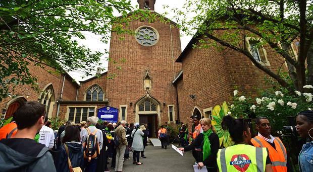 People outside St Helen's Church ahead of a Grenfell Tower memorial service ( David Mirzoeff/PA)