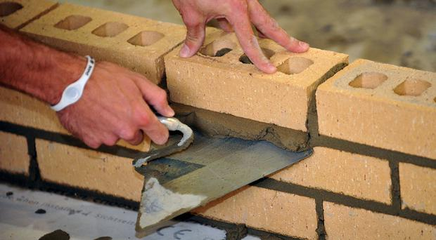 File photo dated 06/10/11 of a trainee bricklayer.