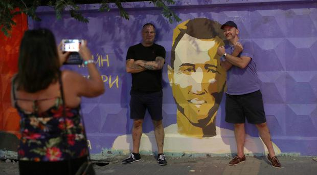 Fans pose for a picture by a mural of England's Harry Kane in Volgograd (Aaron Chown/PA)
