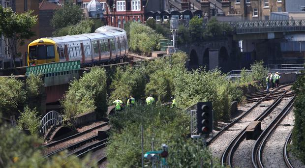 Police on a track near Loughborough Junction railway station, where three people died (Yui Mok/PA)
