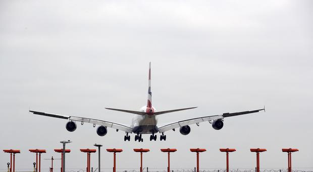 A plane lands at Heathrow Airport (Steve Parsons/PA)