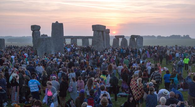 People watch the sunrise at Stonehenge in Wiltshire on the Summer Solstice (Steve Parsons/PA)