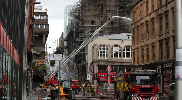 Firefighters dampen down following the fire at the Glasgow School of Art (Andrew Milligan/PA)