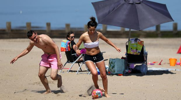 A couple play football on Portobello beach as they take advantage of the hot weather sweeping across the country (Andrew Milligan/PA)