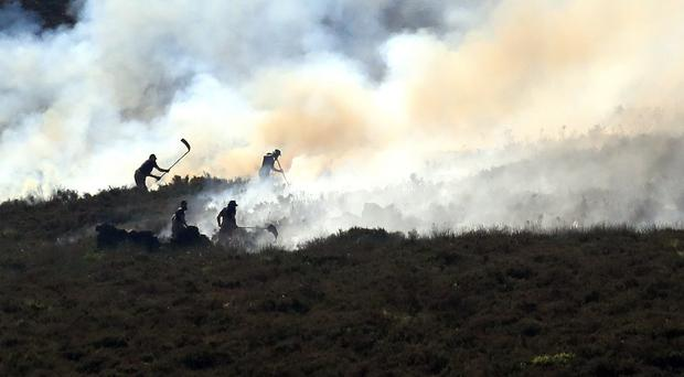 Firefighters tackle the wildfire on Saddleworth Moor (Peter Byrne/PA)