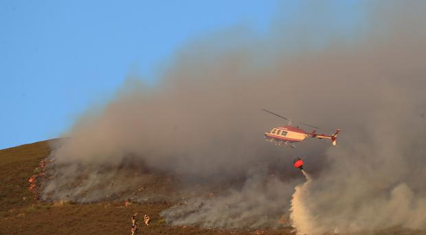 A helicopter drops water as firefighters tackle the wildfire on Saddleworth Moor (Peter Byrne/PA)