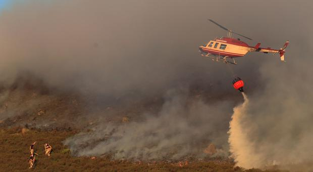 A helicopter drops water as firefighters tackle the wildfire near Saddleworth Moor (Peter Byrne/PA)