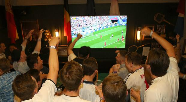 England supporters celebrate Jesse Lingard's goal at a pub in London as fans watch the World Cup match against Panama (Nigel French/PA)