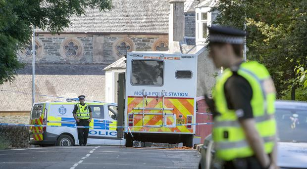 A police cordon on Ardbeg Road on the Isle of Bute in Scotland, after officers found the body of a young girl on the site of the former Cames Hydro Hotel following a report of a six-year-old girl missing in Rothesay (Jane Barlow/PA)