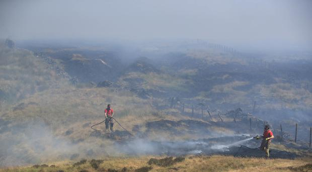 Firefighters from Tyne and Wear Fire and Rescue Service tackle the fire on Winter Hill near Bolton (Peter Byrne/PA)