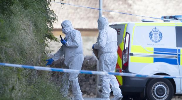 Forensic officers at the police cordon on Ardbeg Road on the Isle of Bute in Scotland (Jane Barlow/PA)