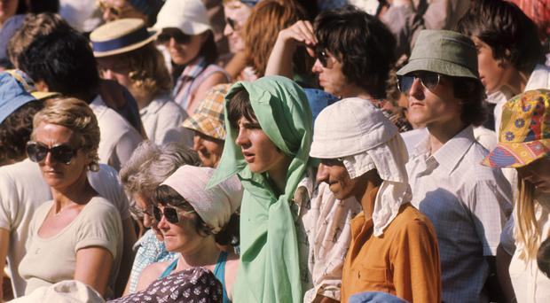 Centre Court fans at Wimbledon cover up for protection against the scorching sunlight in 1976 (PA)