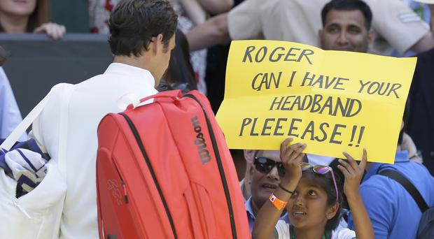A fan holds a banner next to Roger Federer asking for his headband (Tim Ireland/AP)