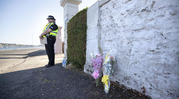 Floral tributes near a house on Ardbeg Road (Jane Barlow/PA)