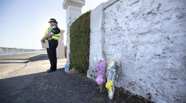 Floral tributes near a house on Ardbeg Road on the Isle of Bute in Scotland (Jane Barlow/PA)