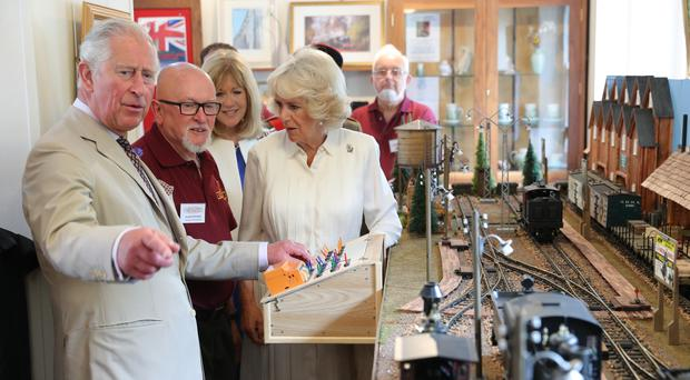 The Prince of Wales and the Duchess of Cornwall try out a model during a visit to Llandovery Railway Station to mark the 150th anniversary of the Heart of Wales railway line (Andrew Matthews/PA)