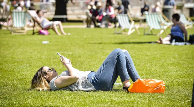 People relax in the sunshine (Ben Birchall/PA)