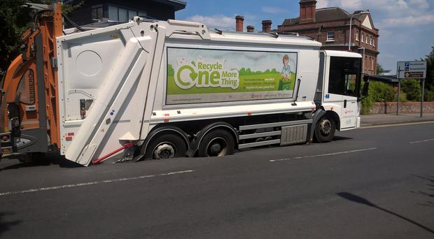A bin lorry working for West Berkshire Council which became stuck after the carriageway gave way after the summer heat melted the asphalt in Newbury (Thames Valley Police/PA)