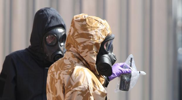 Investigators in chemical suits remove an item as they work behind screens erected in Rollestone Street, Salisbury (Yui Mok/PA)