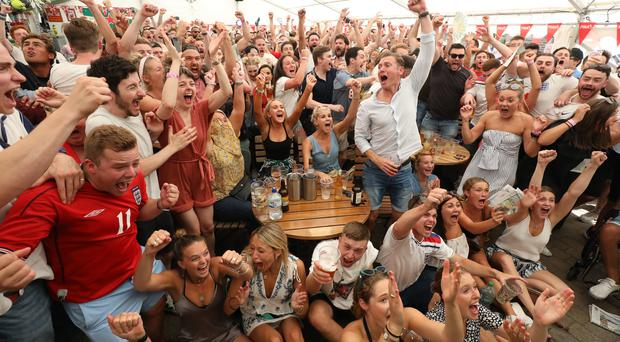 England fans celebrate the first goal from Harry Maguire in the quarter-final match between Sweden and England at the Rose and Crown pub, in Wimbledon (Philip Toscano/PA)