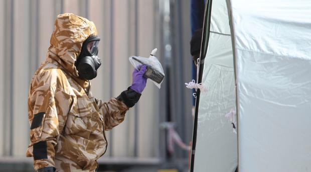 An investigator in a chemical suit removes items as they work behind screens erected in Rollestone Street, Salisbury, Wiltshire, where counter-terrorism officers are investigating (Yui Mok/PA)