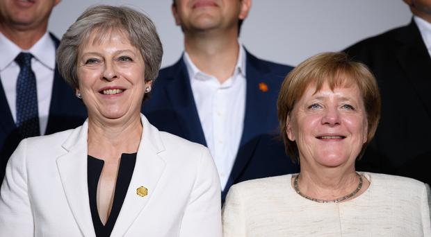 Theresa May and Angela Merkel take part in the family photo during the second day of the Western Balkans summit at Lancaster House, London (Leon Neal/PA)