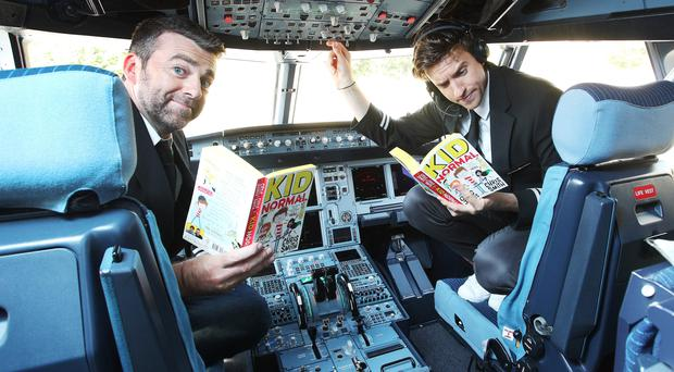 Greg James and Chris Smith, authors of Kid Normal, help easyJet launch 300 'Flybraries' at Gatwick Airport (easyJet/PA)