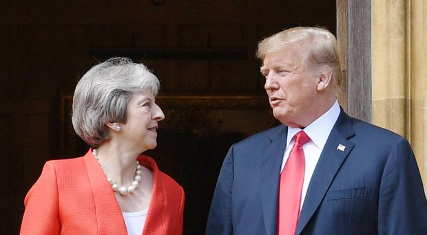 US President Donald Trump stands with Prime Minister Theresa May on the doorstep at Chequers, after he arrived for talks at her country residence in Buckinghamshire (Stefan Rousseau/PA)