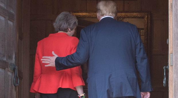 Theresa May and Donald Trump walk through the doors at Chequers after he arrived for talks at her country residence in Buckinghamshire (Stefan Rousseau/PA)
