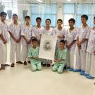 The rescued soccer team pose with a sketch of Saman Gunan