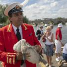 The Queen's Swan Marker David Barber holds a cygnet during the ancient tradition of counting swans along the River Thames (Steve Parsons/PA)