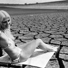 19-year-old model Cerica, tanning herself in the dried-up basin of Pitsford Reservoir in Northamptonshire (PA)