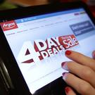 A woman viewing a sale being promoted on the Argos website (Yui Mok/PA)