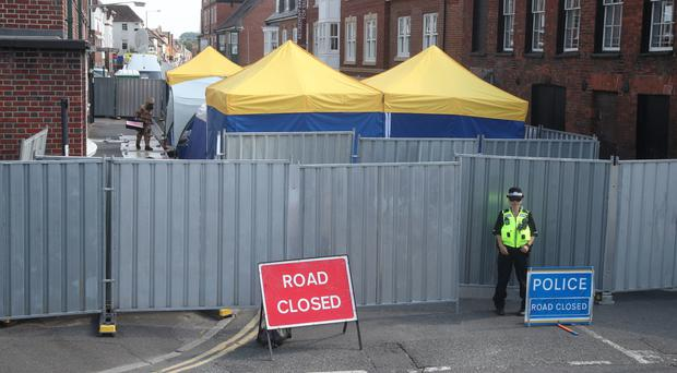 An investigator wearing protective clothing works behind screens erected in Rollestone Street, Salisbury, Wiltshire (Yui Mok/PA)