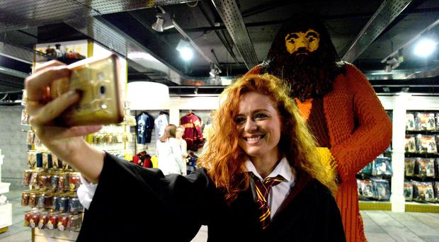 A staff member takes a selfie with a statue of Hagrid at Hamleys (Kirsty O'Connor/PA)