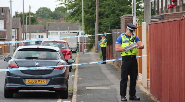 Police at the scene in Wolverhampton, where a man in his 20s was fatally shot dead overnight.